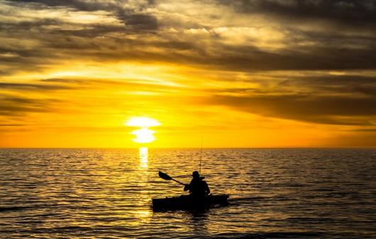 Рыбак на закате в лодке