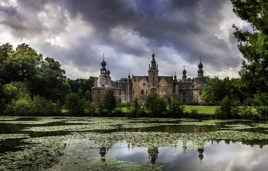 Старинный замок на берегу пруда в Бельгии