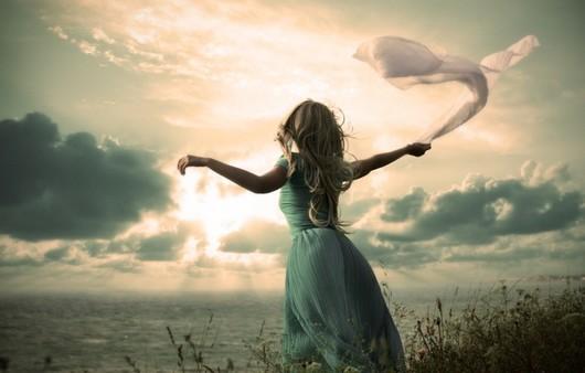 Девушка с развивающимся шарфиком в руках перед морем