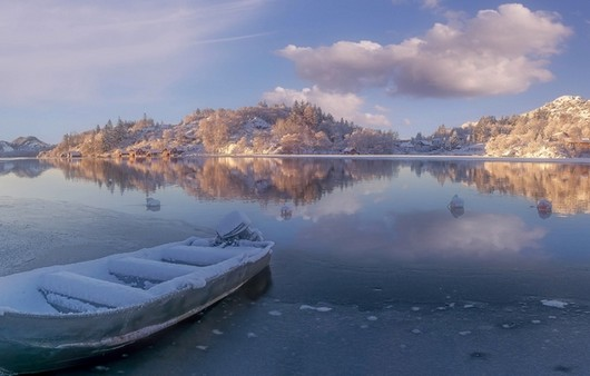Лодка на причале на заснеженной реке