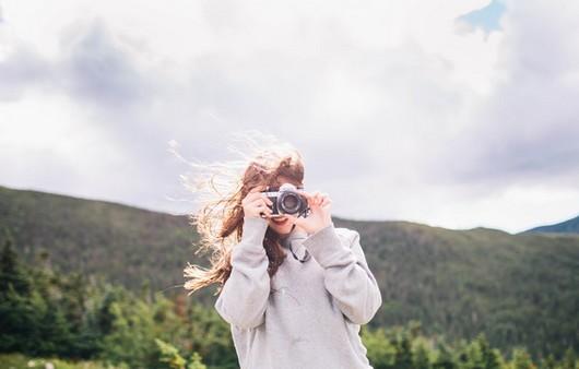 Девушка с фотоаппаратом в горах