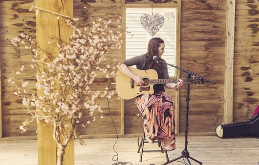 Девушка с гитарой на высоком табурете