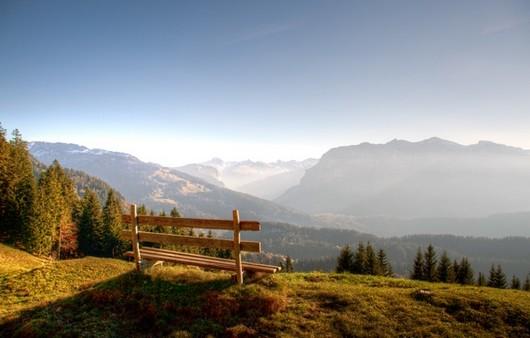 Скамейка на высоком холме с панорамой гор