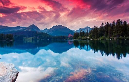 Водяная гладь озера с отражением облаков