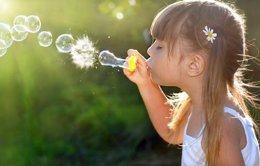 Девочка пускает мыльные пузыри