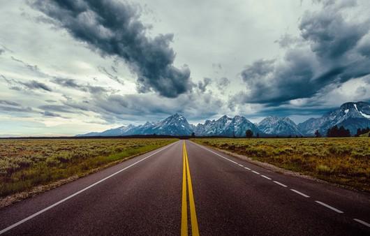 Пейзаж дороги и горного массива на горизонте