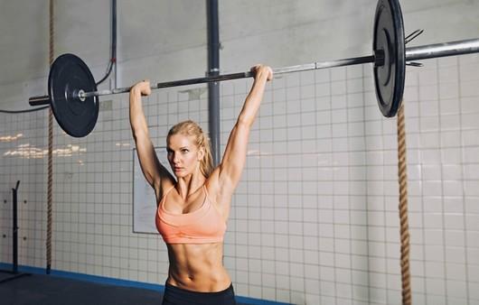 Спортивная девушка со штангой