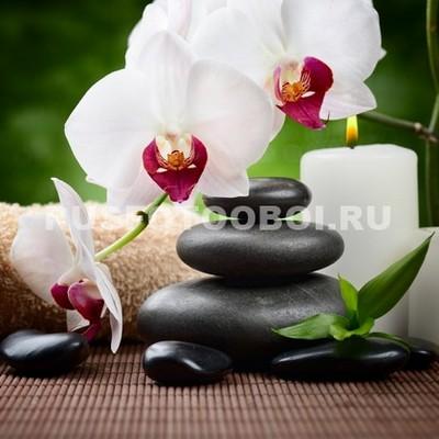 Белая орхидея со свечой и галькой