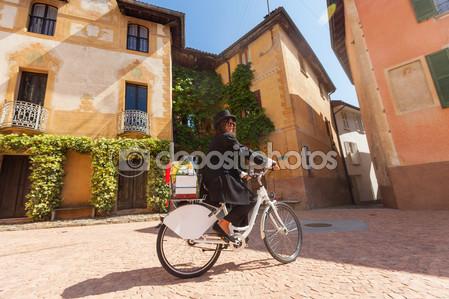 Женщина на велосипеде по улицам страны